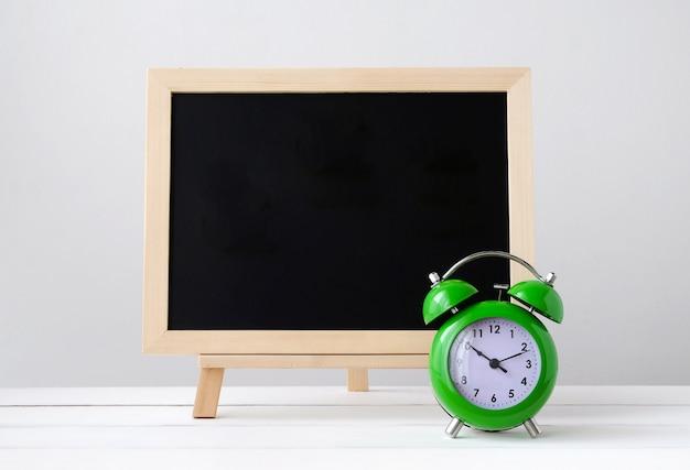 緑の目覚まし時計、白いテーブル上の空のブラックボード
