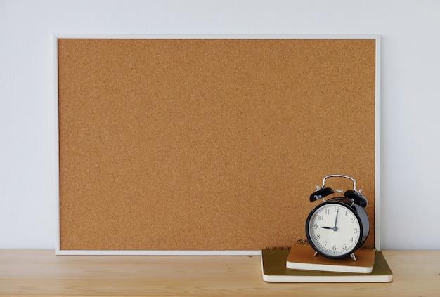 木製テーブル上のノートブックと目覚まし時計