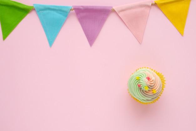 ピンクの背景にパステルカップケーキとカラフルなパーティーの旗