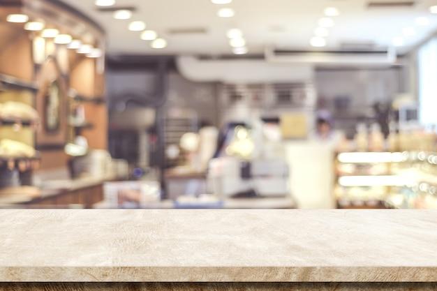 ぼかしカフェの背景、製品、食べ物の表示モンタージュの上に空の茶色のセメントのテーブル