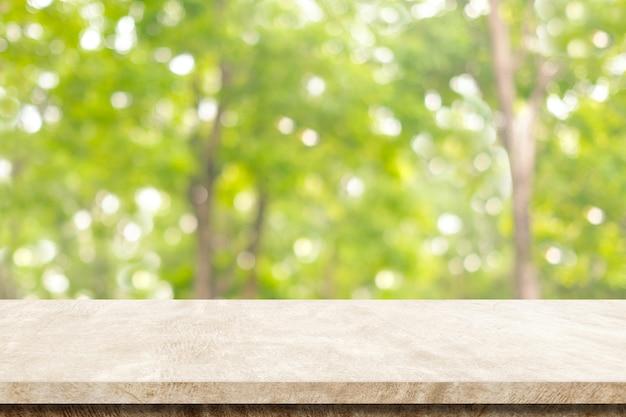 ぼんやりとした茶色のセメントのテーブルぼんやりとした緑の自然公園の背景、