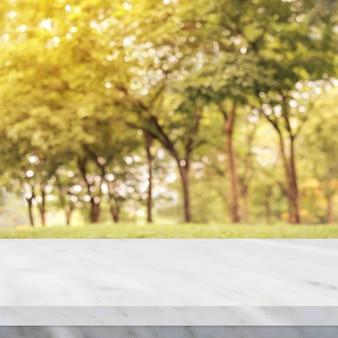 ぼんやりとした白い大理石のテーブル秋の自然公園の背景、製品のディスプレイのモンタージュ