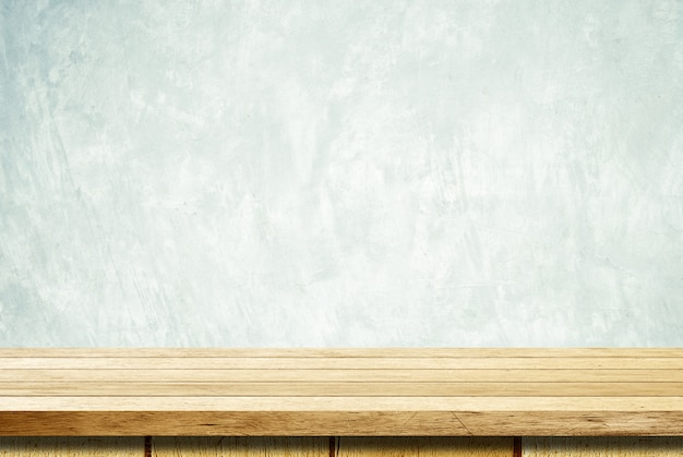 グランジセメント壁の背景の上の空の木製テーブル