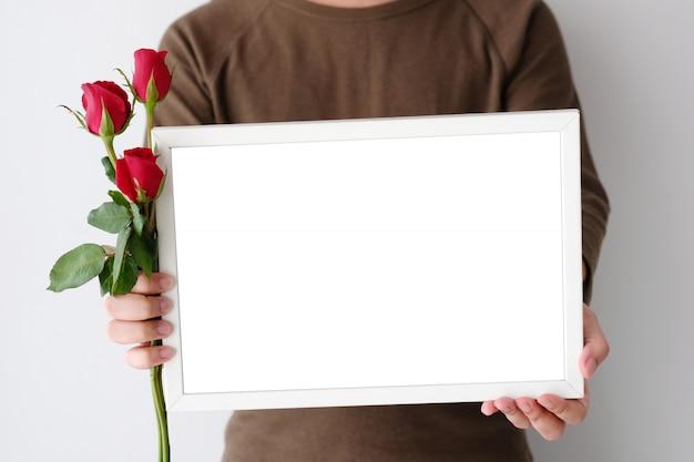 赤いバラと白い背景の上に立っている空白の白い木製フレームを持っている男の手