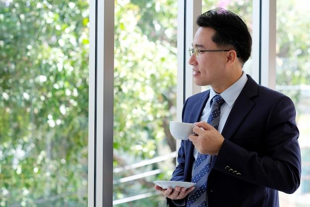 窓のそばに立ってコーヒーカップを保持しているアジア系のビジネスマン