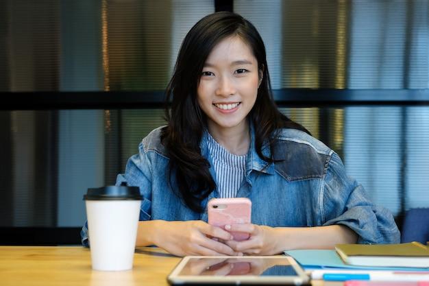 彼女のオフィスの机でスマートフォンを使用して若いアジア女性
