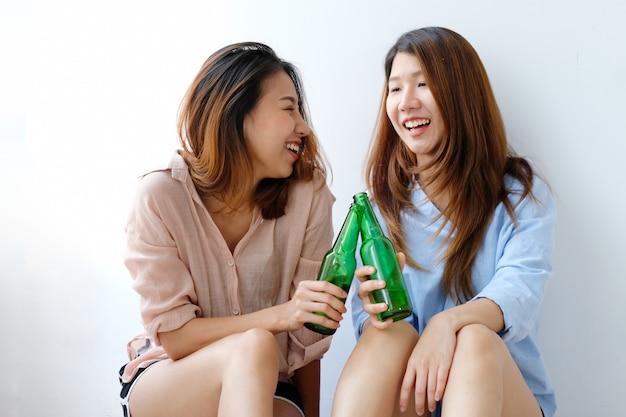 Две азиатские женщины пьют пиво на вечеринке, празднике, лгбт-паре, образе жизни