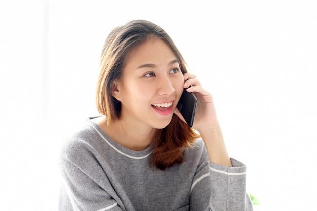 Телефон молодой азиатской женщины говоря на белой предпосылке