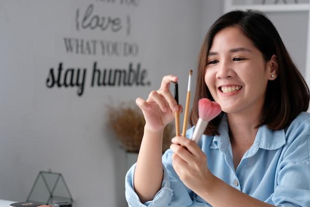 Молодой азиатский блоггер красоты женщины показывая как составить видео- учебную запись камерой