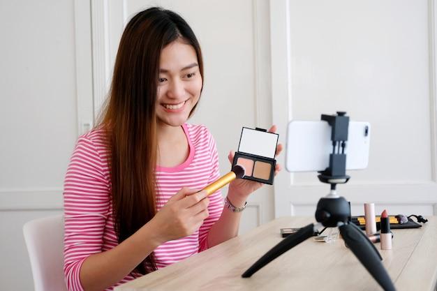 スマートフォンで録画しながらビデオチュートリアルを作成する方法を示す若いアジア女性美容ブロガー