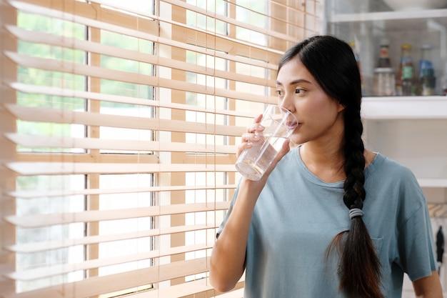 若い美しいアジアの女性がキッチンの背景の窓のそばに立っている間水を飲む