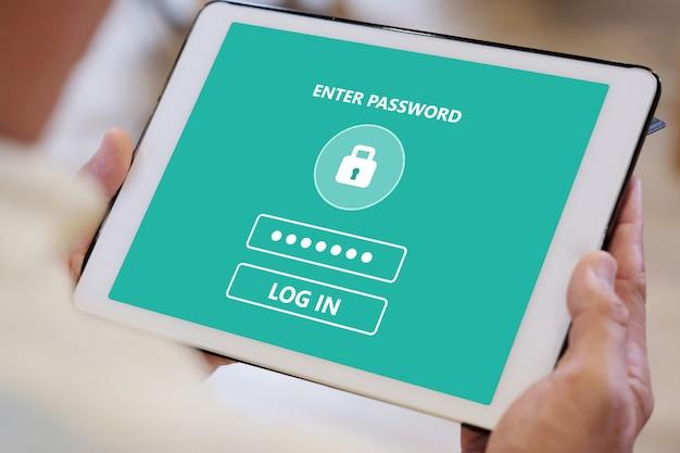 年配の男性人の手が画面にパスワードログインでタブレットを使用して
