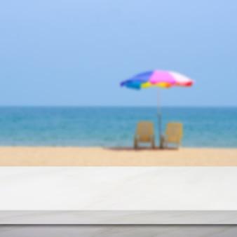 空の白い大理石のテーブルの上にカラフルな傘と青い空と海のビーチをぼかし