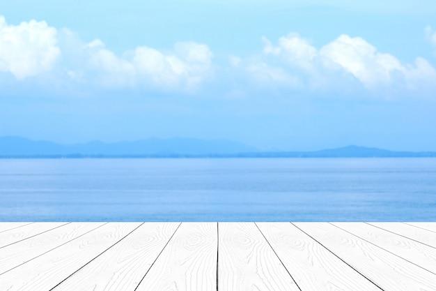 Пустой белый мраморный столик над размытым синим морем и небом летом