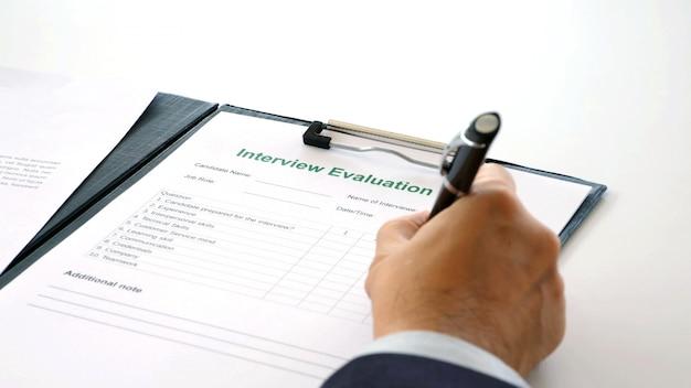 Рука человека, проверка бумаги оценки интервью для собеседования в офисе