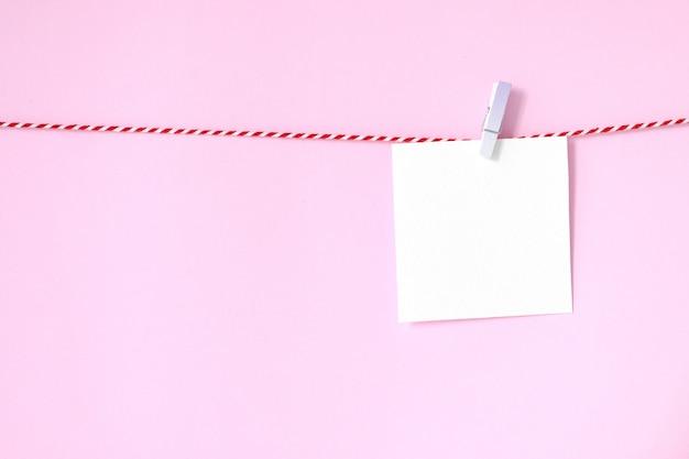 テキストのコピースペースで、ピンクの背景に掛かっている空白のホワイトペーパーのメモ帳