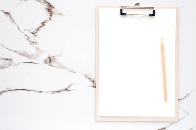 白紙のメモ用紙と白い大理石の背景にクリップボードに鉛筆