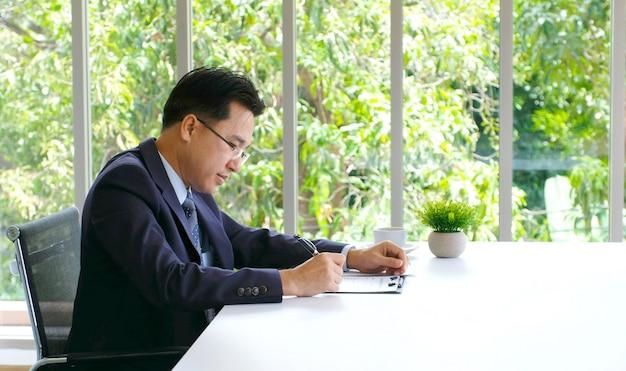 彼のオフィスの机でドキュメントに取り組んでいる上級のアジア系のビジネスマン