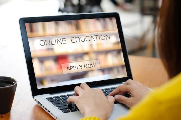 Женщина вручает печатать портативный компьютер с онлайн образованием на экране, онлайн обучением, концепцией образования