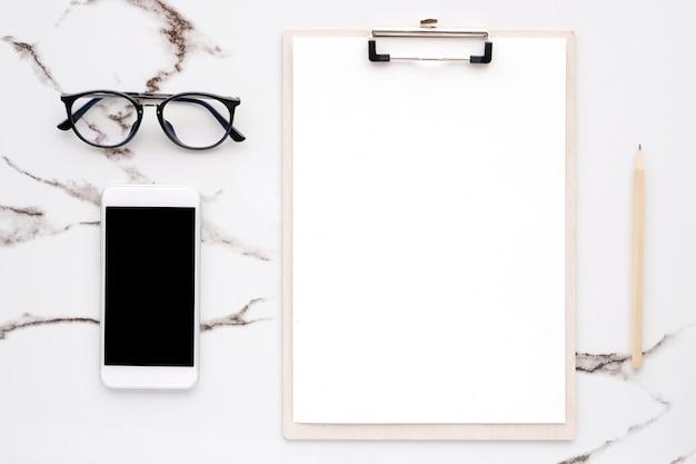 白紙のメモ用紙、スマートフォン、鉛筆、白い大理石の眼鏡