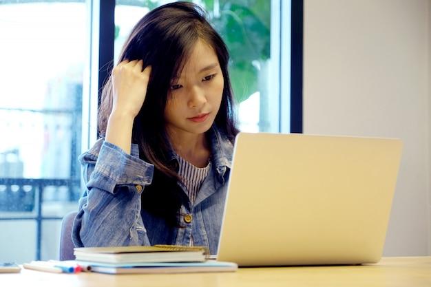 Молодая азиатская женщина с разочарованным выражением пока работающ с компьтер-книжкой