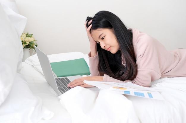 Молодая азиатская разочарованная схватка женщины с портативным компьютером пока лежащ на кровати