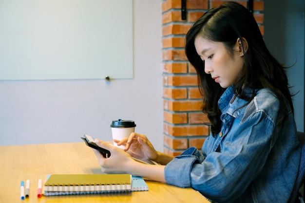 ホームオフィスでデジタルタブレットを使用して若いアジア女性