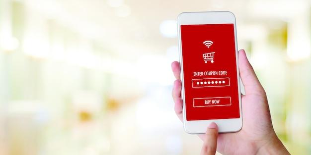 Рука с помощью мобильного телефона с купоном на скидку на экране