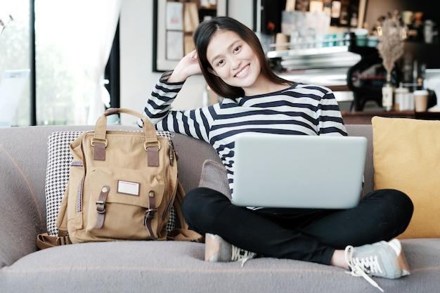 Красивая азиатская девушка, используя портативный компьютер, сидя на диване с улыбкой лицо эмоции, люди и концепция технологии, образ жизни