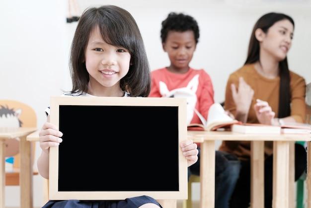 かわいいアジアの女の子、教室、教育の概念の背景で空の黒板を持って