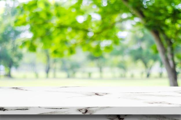 ぼんやりとした白い大理石のテーブル、緑の公園の背景、製品のディスプレイのモンタージュ