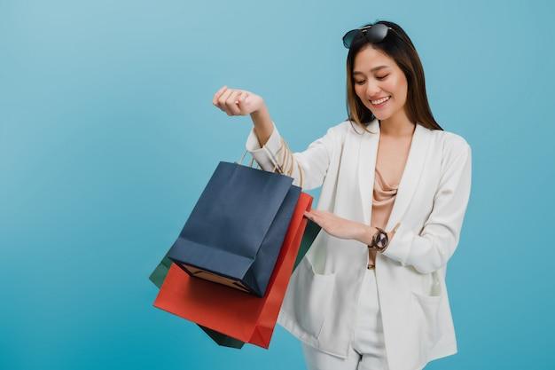 アジアの美しい女性ブロガーは買い物をして買い物袋を保持しています。