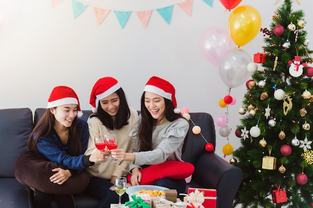 若いアジアの美しい女性は、親友とシャンパンのお祝いを飲みます。ホリデーフェスティバルのクリスマスツリーの装飾が施された部屋で笑顔の顔。クリスマスパーティーやお祝いのコンセプト。