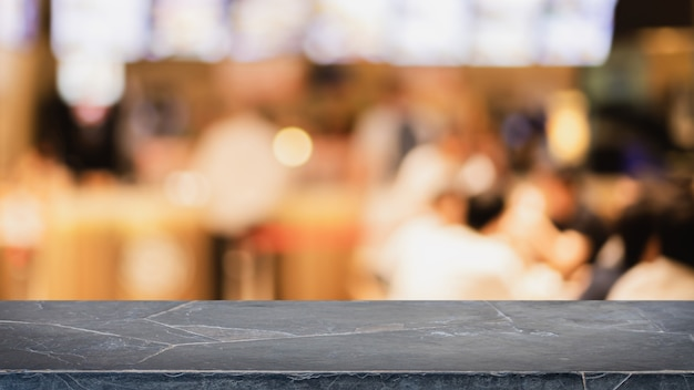 空の黒い大理石の石のテーブルトップとぼけボケカフェとレストランの背景。