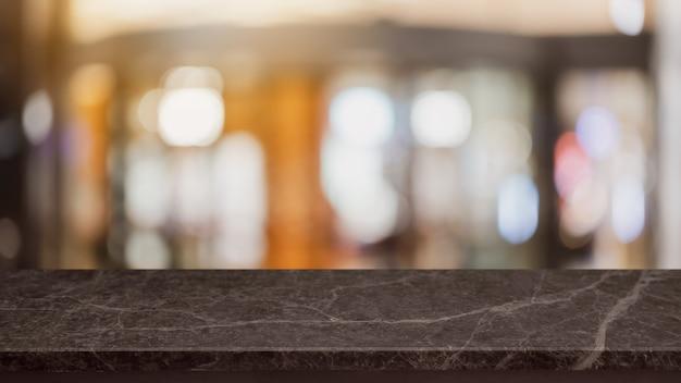 空の黒い大理石の石のテーブルトップとぼやけたコーヒーショップとレストランの背景。