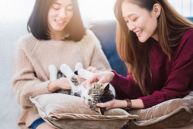 Любовник пар красивых азиатских женщин лесбосский играя милого любимчика кота в живущей комнате дома с усмехаясь стороной. понятие о сексуальности лгбт с счастливым образом жизни вместе.