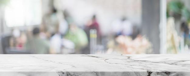 白い大理石の石のテーブルトップを空にし、ガラス窓のインテリアレストランのバナーの背景をぼかし。