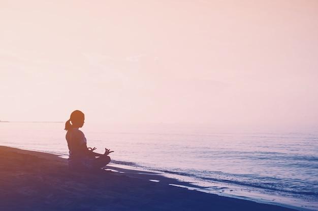 ヴィンテージフィルターでビーチの背景にヨガと女性運動