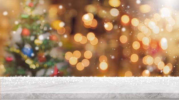 ぼやけたクリスマスツリーのバナーに光のボケ味を持つ空の白い大理石の石のテーブルトップ