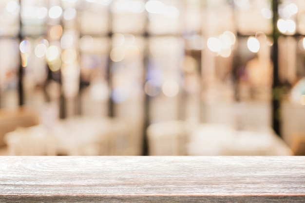空の木のテーブルトップとぼやけたボケカフェとレストランのインテリアの背景。