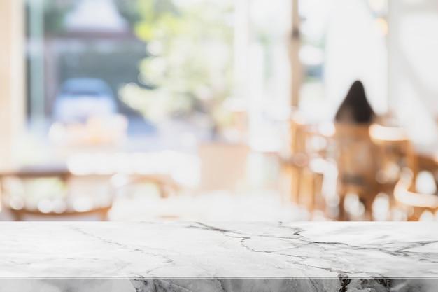 空の白い大理石の石のテーブルの上にボケ味のカフェの背景をぼかした写真。