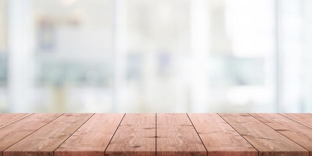 空の木製テーブルトップと抽象的なレストランのインテリアの背景をぼかした写真