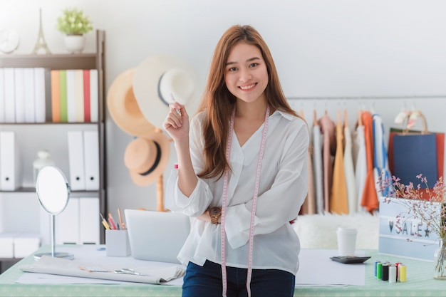 美しいアジアの女性ファッション・デザイナー、衣料品店に立っています。