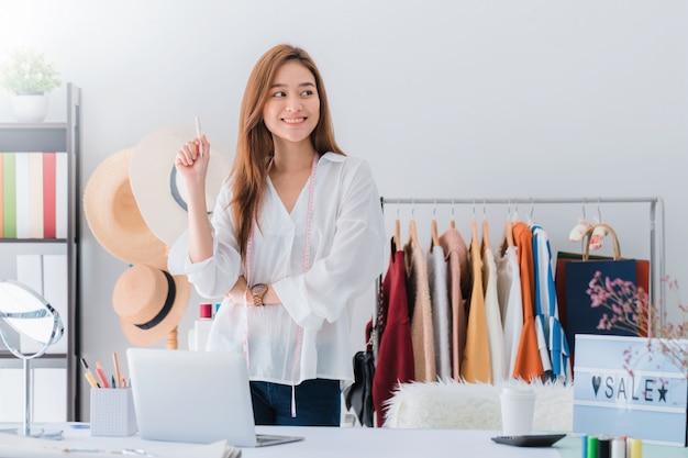 Красивый азиатский модельер женщины стоя в магазине одежды