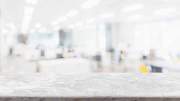 白い大理石の石造りのテーブルトップを空にして、オフィスビルの内部のガラス窓の壁をぼかし