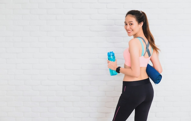 アジアの美しい女性のヨガと白の運動をした後の水のボトルとヨガマット
