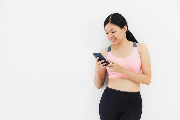 ヨガをし、白い壁で運動した後、スマートフォンを使用してアジアの美しい女性