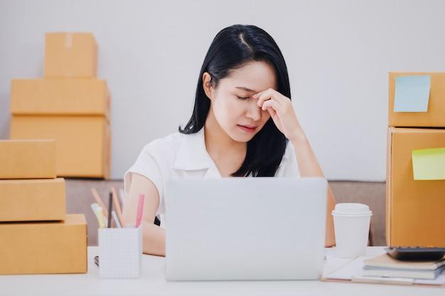 Азиатская красивая молодая коммерсантка чувствуя головную боль и стресс в размерах офиса с коробкой продукта.