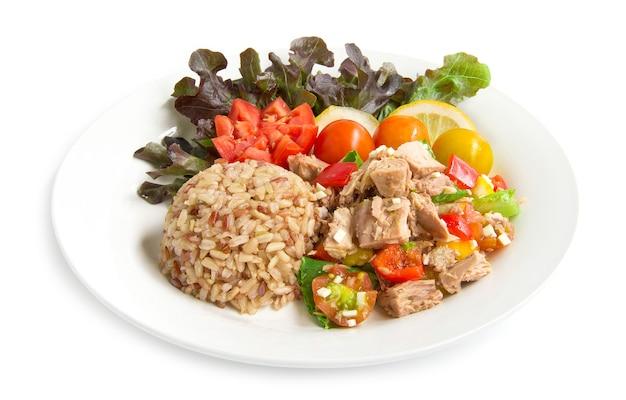 Коричневый рис с салатом из тунца прозрачный соус здоровая пища чистые продукты украшают резными помидорами, дольками лимона и листьями красного дуба, вид сбоку изолирован
