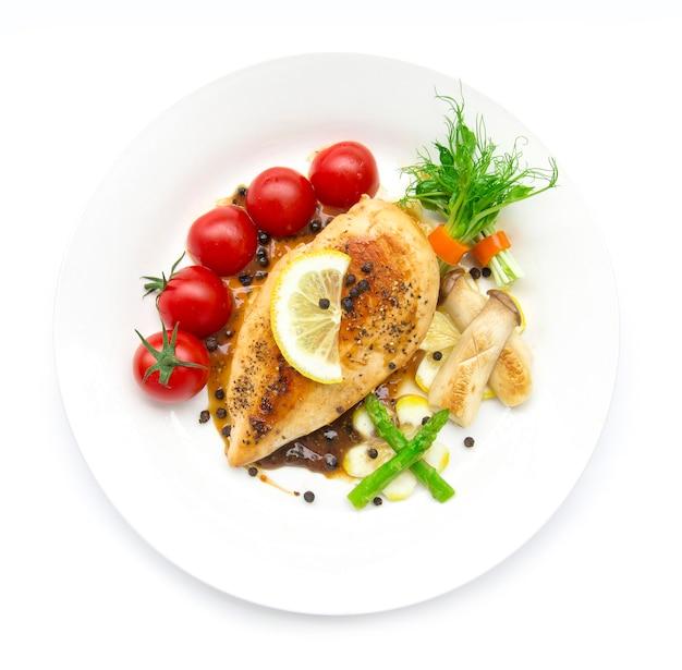 Гриль куриная грудка или стейк из курицы с соусом из черного перца, увенчанный черным перцем, украшают спаржу, вешенку, помидоры и лимон, вырезанные в стиле сверху, на белом фоне